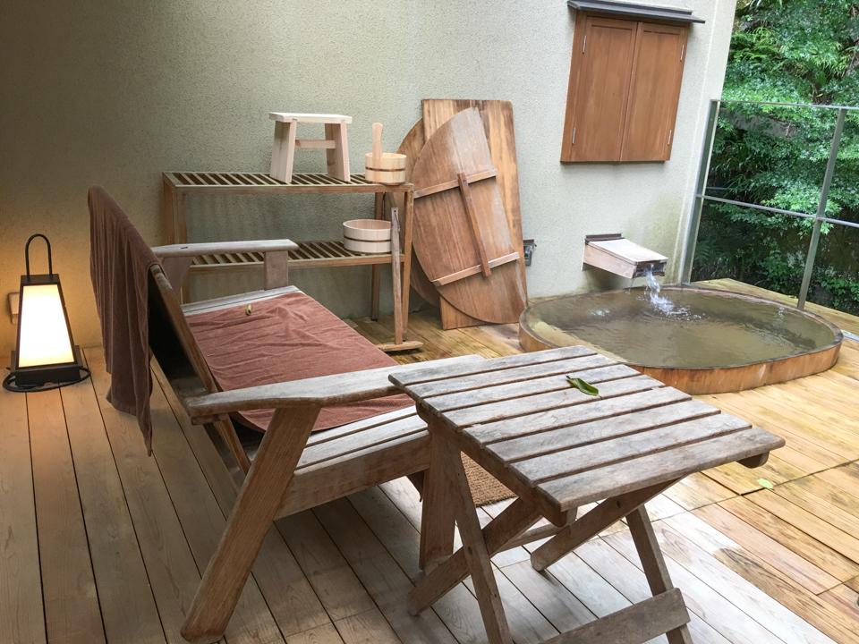 露天風呂の浴槽横、休憩用の椅子の写真