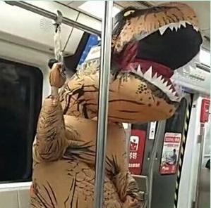 恐竜の着ぐるみを着て電車に乗っている写真