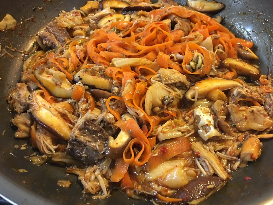 キムチと野菜と鯖水煮を煮ている写真