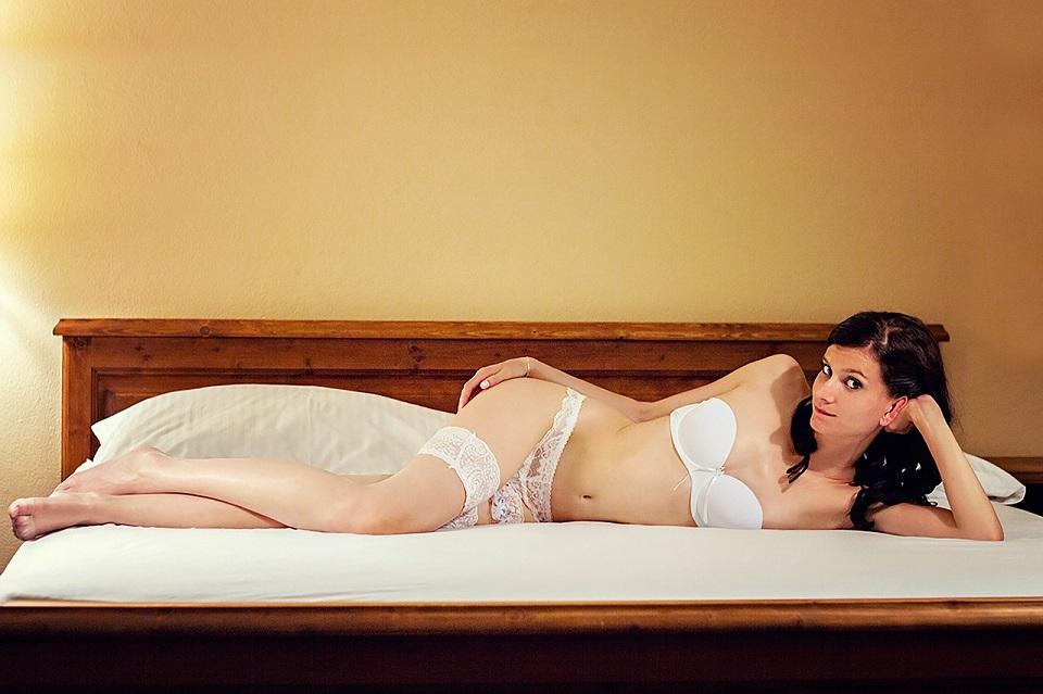 美しい女性がベッドに横になって下着姿で待っている写真