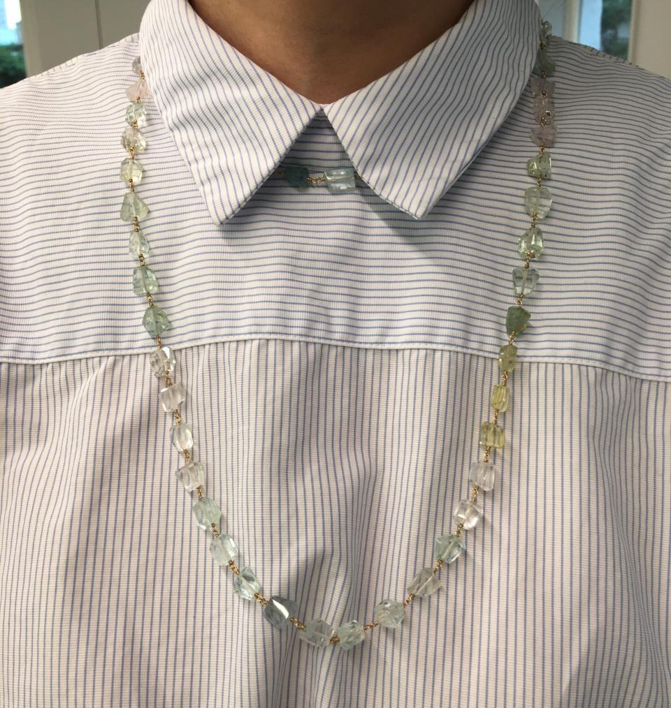 パステルカラーの石のネックレスを長短重ね付けしている筆者写真