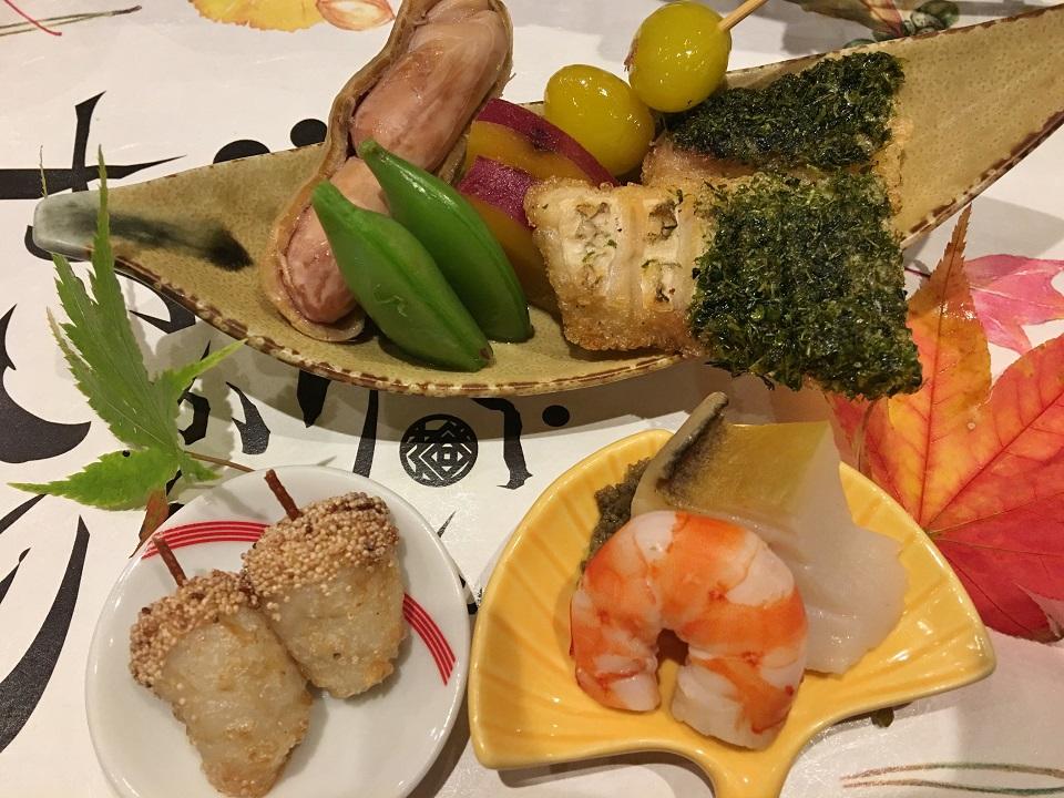 白身魚の焼きもの、落花生、里芋などの写真