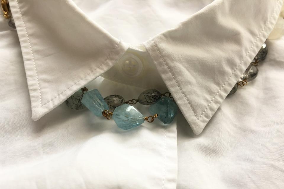 白いブラウスの襟から水色の石を見せた写真