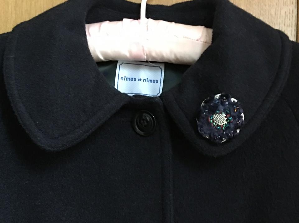 マビーユのブローチをコートにつけている写真