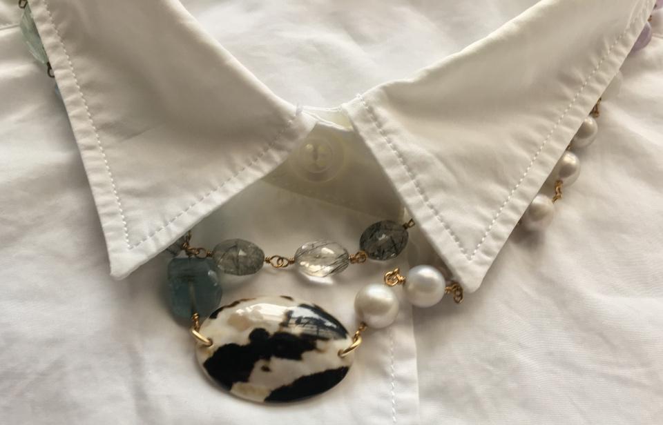 白いブラウスの襟からストライプの石を見せた写真