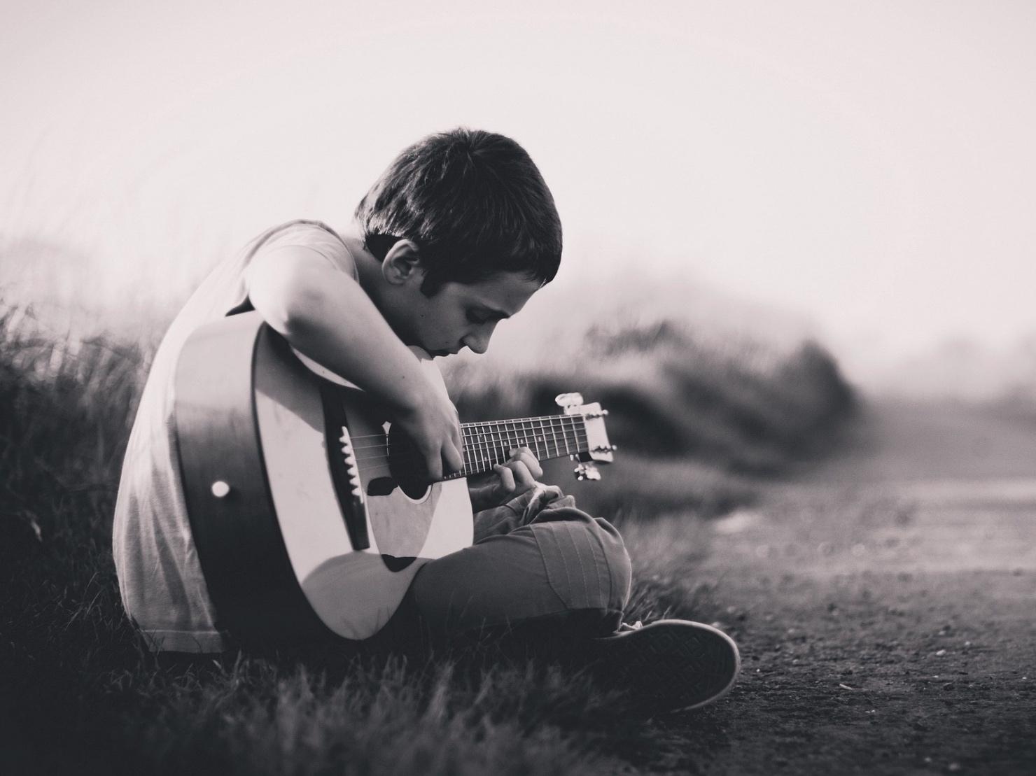 ギターを弾く少年の写真