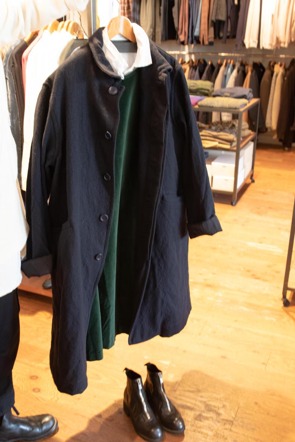 白いブラウス、緑のワンピース、濃紺のジャケット、黒い靴をコーディネートしている写真