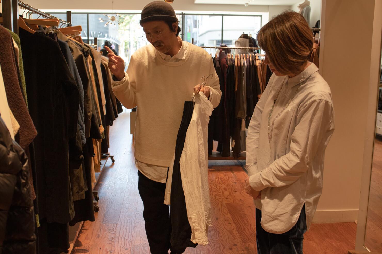 浅田さんがケーシーケーシーのブラウスとスカートを持っている写真