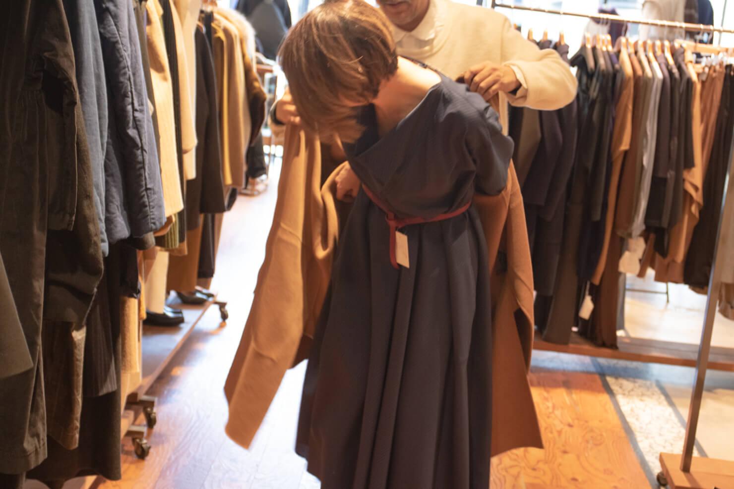 ソフィドールのワンピースの上にコートを着せてもらっているガッツの写真