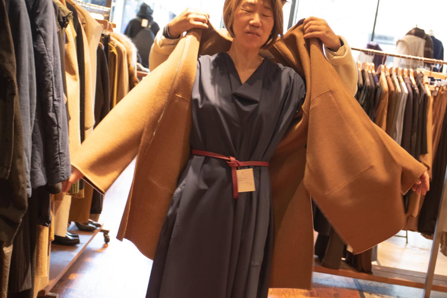 ソフィドールのAラインのワンピースの上にコートを着せてもらっている写真