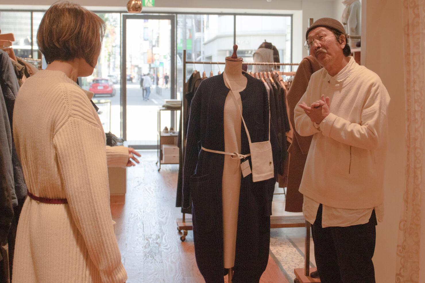 ロングカーディガンを着ているマネキンとの横でオネエポーズをする浅田さんの写真