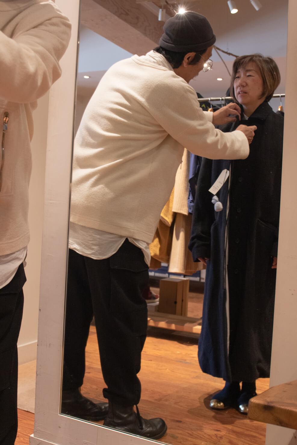 コートの襟を浅田さんが直している写真