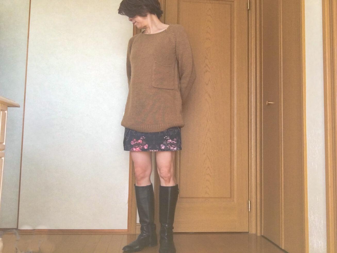 ミニスカートとベージュのニットの写真