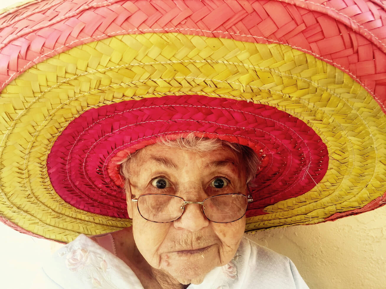 色あざやかな帽子をかぶった高齢女性の写真