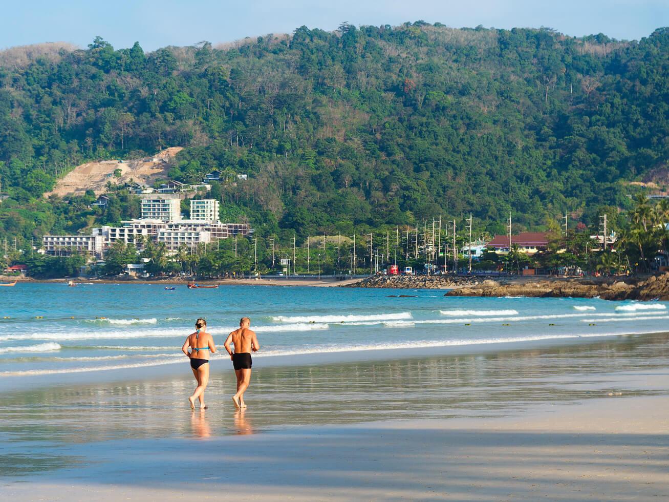 ビキニで海岸を走る女性の写真