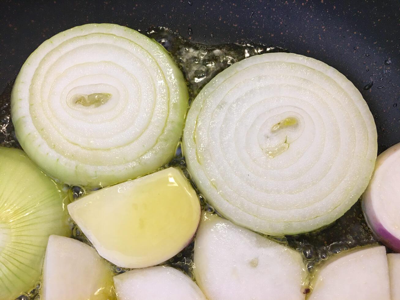玉ねぎをフライパンで焼いている写真