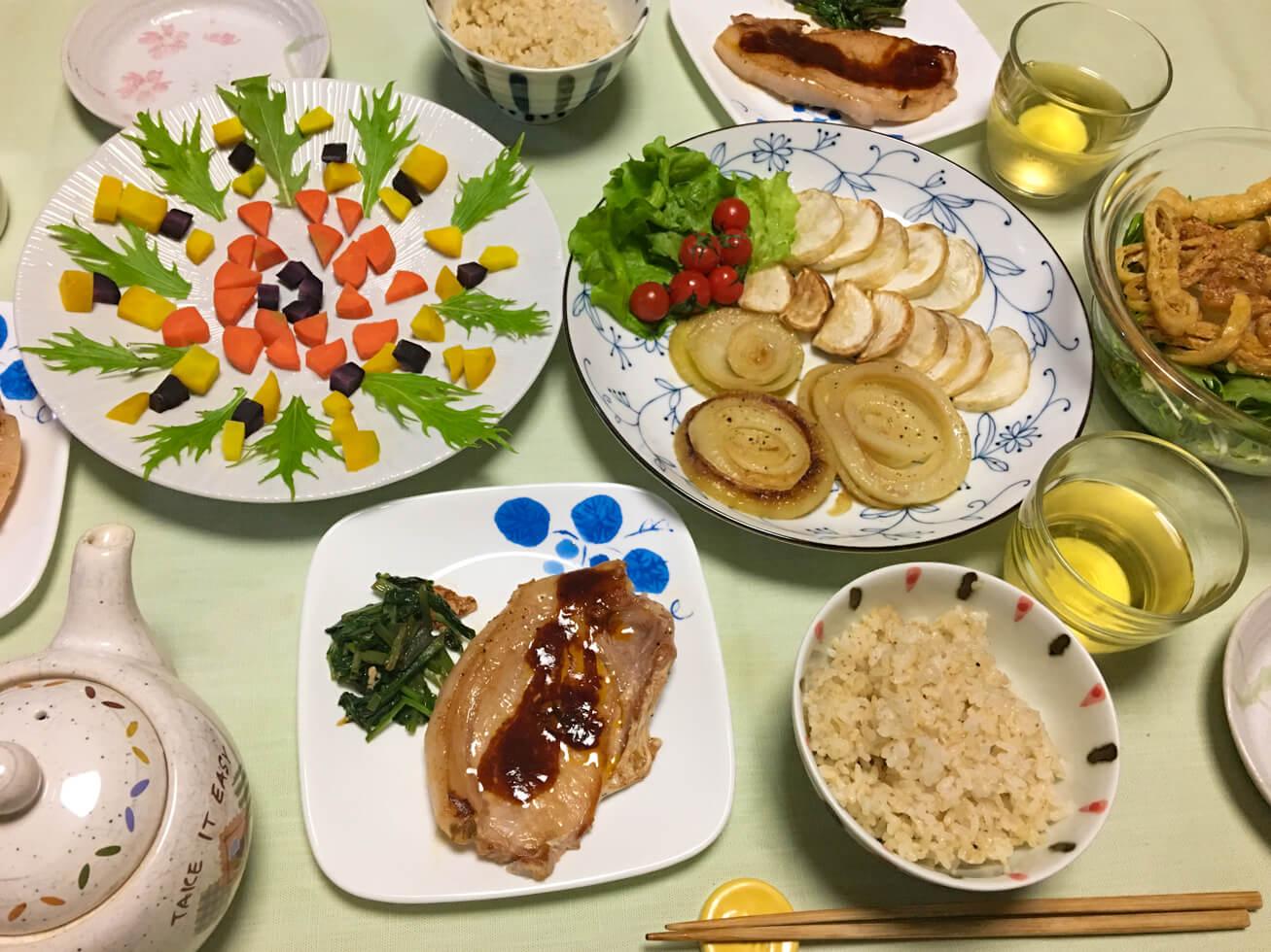 カラフル人参や焼いた玉ねぎのある食卓の写真