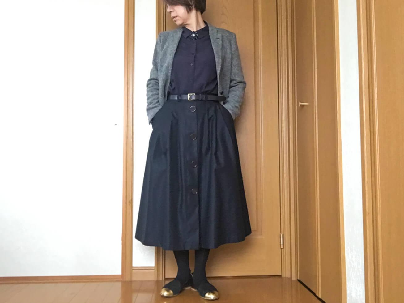 紺のブラウスとチェックのジャケットのおしゃれコーデの写真
