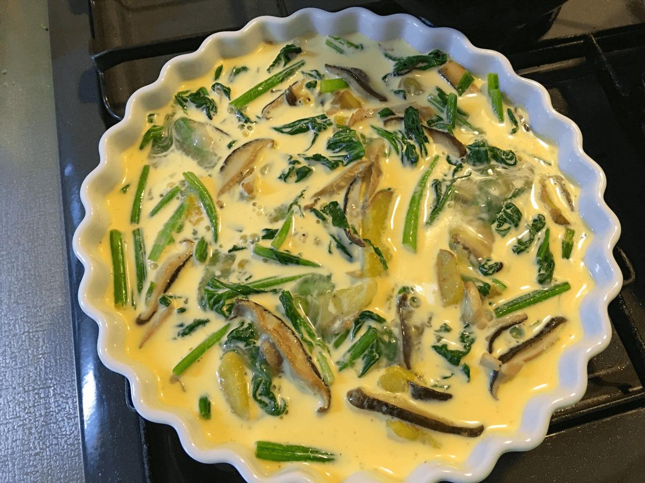 ほうれん草とシイタケのキッシュの具ををパイ皿に移して卵液をかけた写真