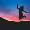 夕陽を背にジャンプする女性の写真