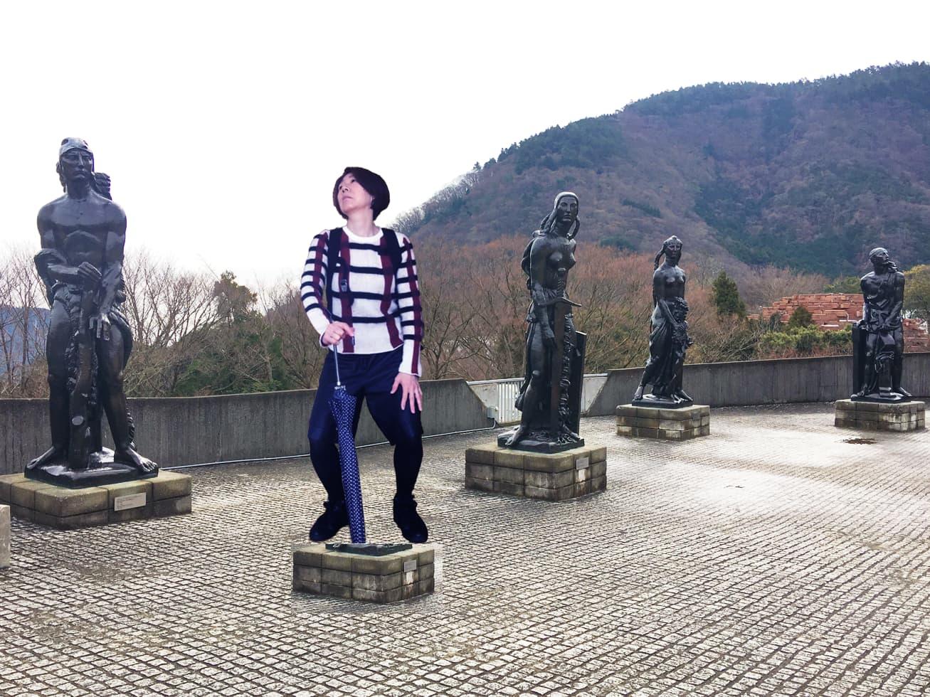 50代旅行コーデで彫刻の隣でポーズをとるガッツの写真