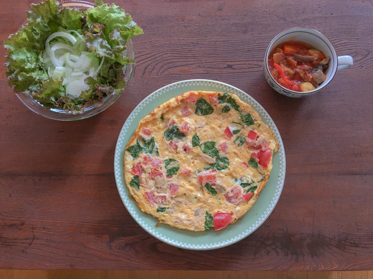 バジルとトマトとツナのオープンオムレツ中心の晩御飯の写真