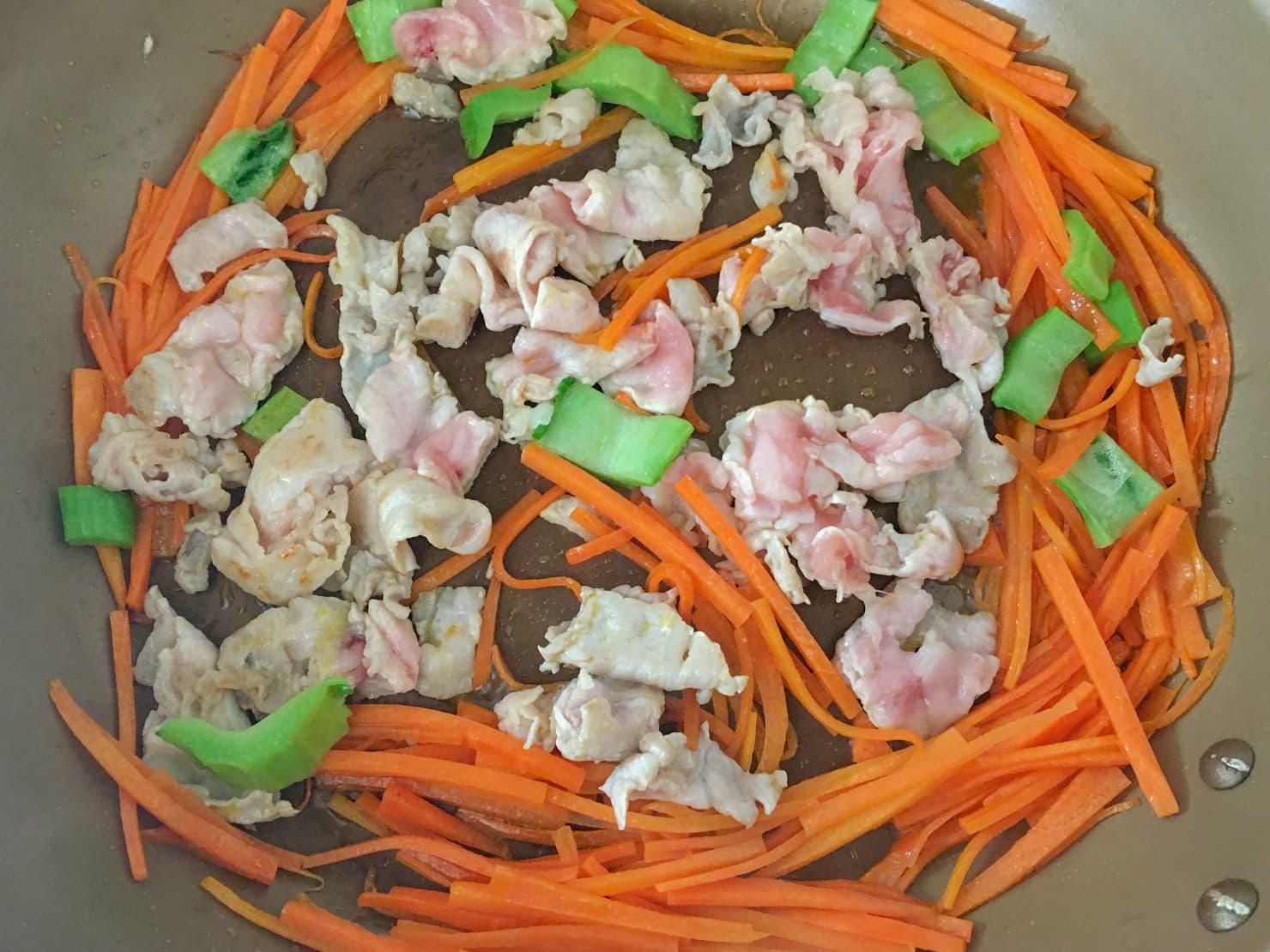 豚肉とかつお菜の茎を炒めているところの写真